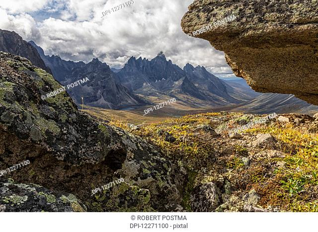 Tombstone Mountain is framed by rocks in this view within Tombstone Territorial Park; Yukon, Canada