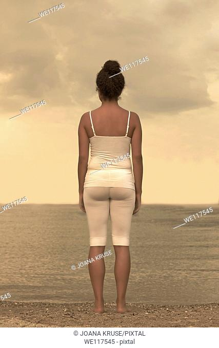 a woman is standing in white sports clothes on the shore of a lake