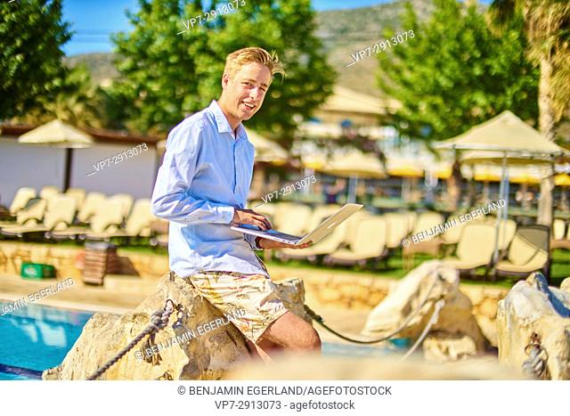 young business man with laptop computer in holiday destination