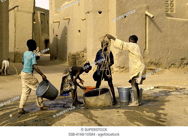 Mali, Djenne, Street Scene Children Getting Water From Well