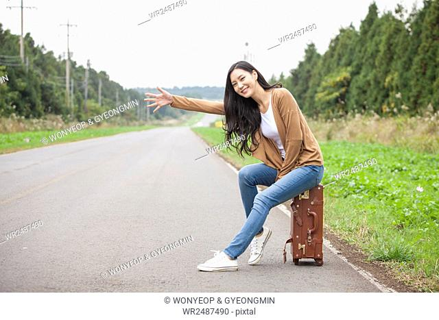 Young smiling woman sitting on a carrier and trying to hitch a ride on a road