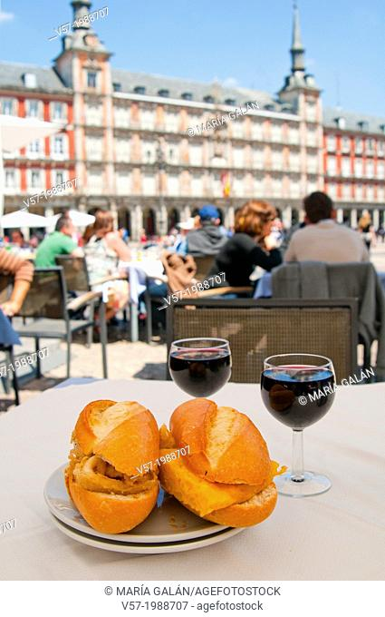 Fried squids sandwich and Spanish omelette sandwich with glasses of red wine on a terrace. Main Square, Madrid, Spain