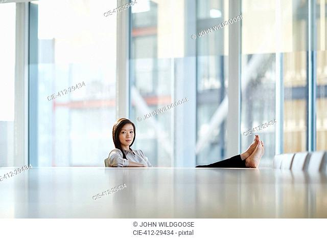 Portrait confident businesswoman with bare feet up on conference room table