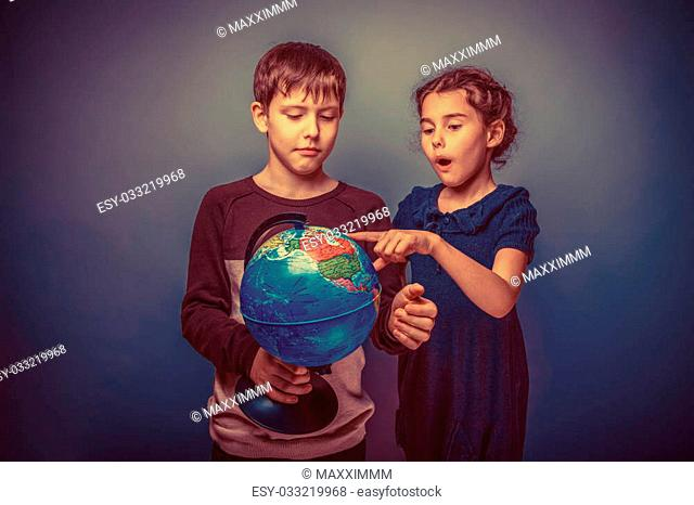Teen boy and girl of European appearance seven years are holding a globe on his finger show a gray background, travel, emotions retro