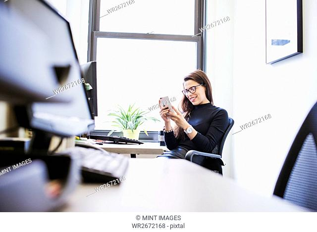 A young woman sitting at a desk in an office looking down at a cellphone