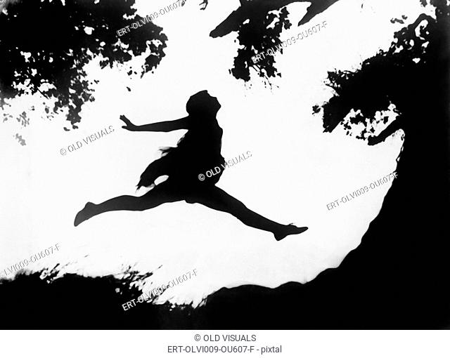 Silhouette of a woman leaping in mid-air