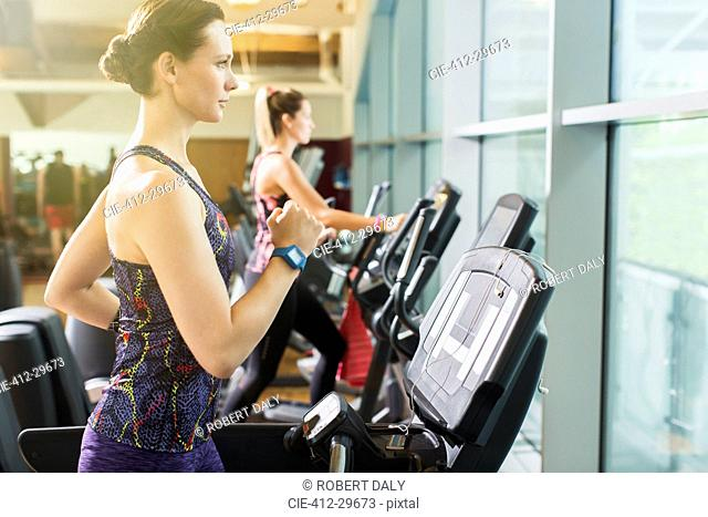 Focused woman running on treadmill at gym