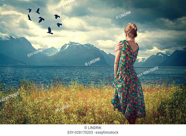 Girl in Iceland is in a dress on the shore of the fjord, and looking at the birds