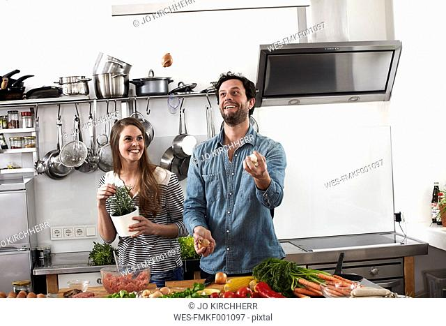 Man juggling with food in kitchen