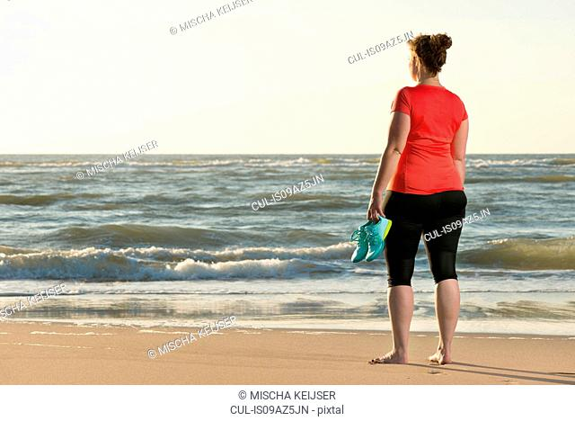 Mature woman standing on beach at sunset, after running