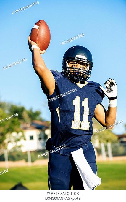 Teenage american footballer holding up ball on pitch