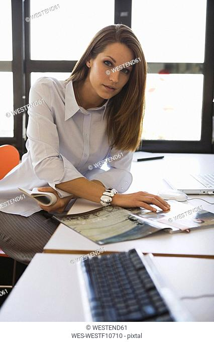 Young woman in office reading magazine, portrait