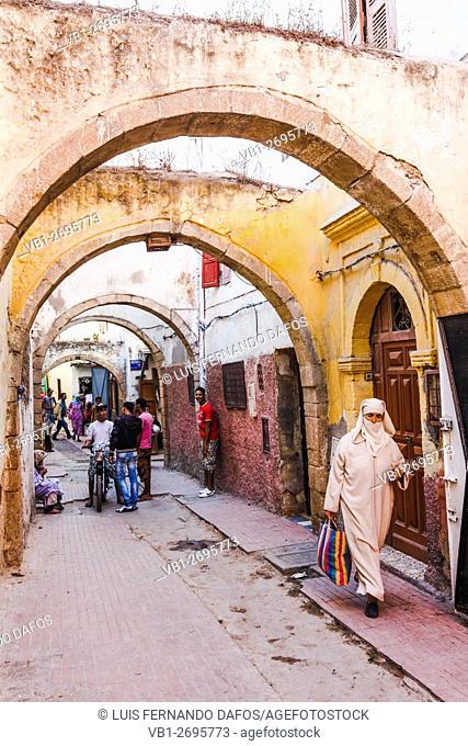 Veiled woman at narrow Lane with arches. Safi medina, Atlantic Morocco