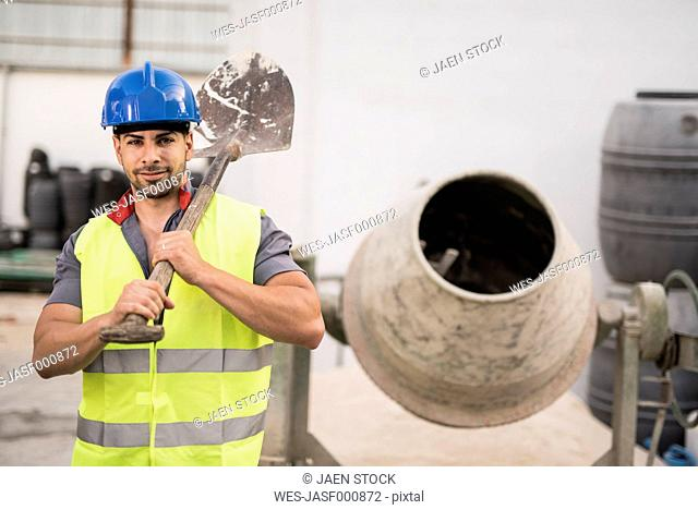 Construction worker next to the concrete mixer