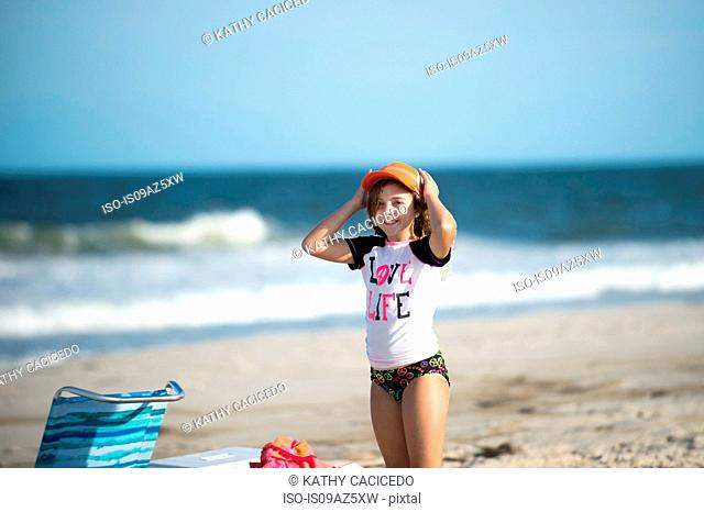 Young girl on beach putting cap on