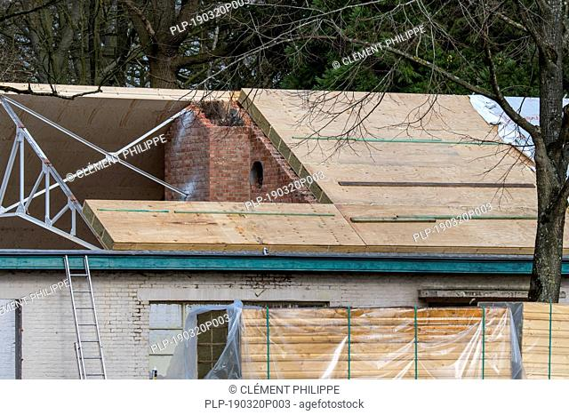 Building fitted with warm pitched roof insulation by installing insulating sandwich panels