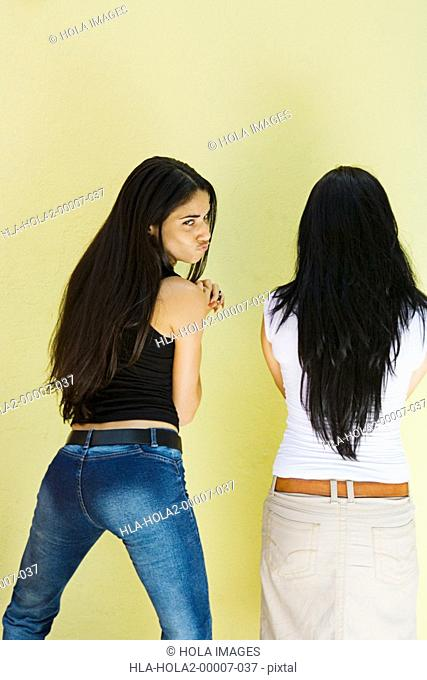 Two young women standing against wall