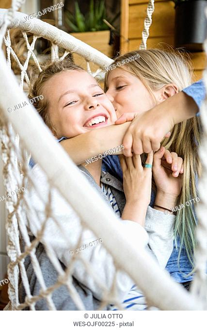Girl hugging and kissing her best friend in a hanging chair