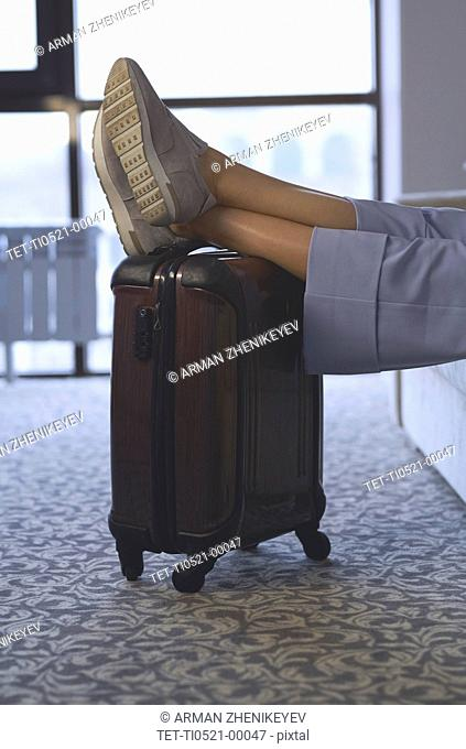 Legs of businesswoman with feet up on luggage