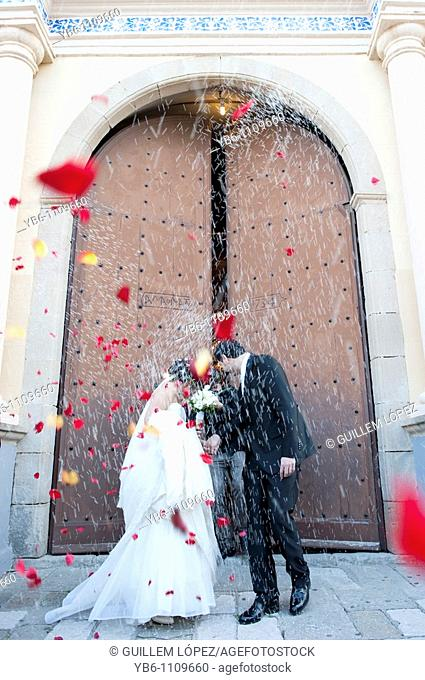 A just married couple coming out of the church with people throwing rice and rose petals to them