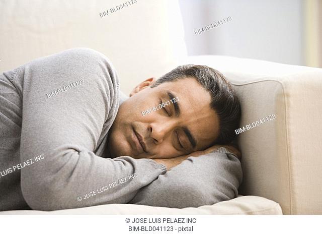 Hispanic man sleeping on sofa