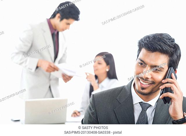 Close-up of a businessman talking on a mobile phone with his colleagues in the background