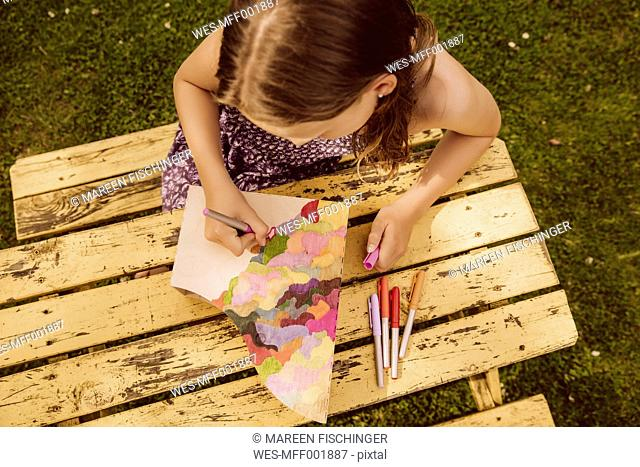 Girl drawing on a wooden magazine file in garden