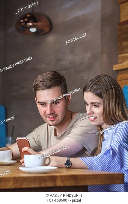 Young couple using mobile phone while sitting at restaurant