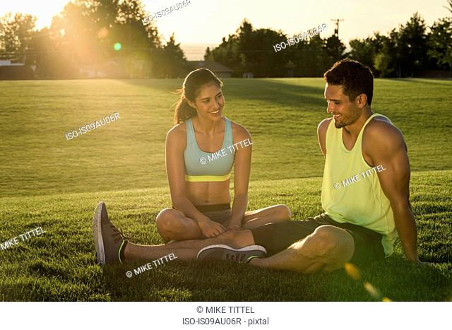 Young man and woman taking a break from training in park