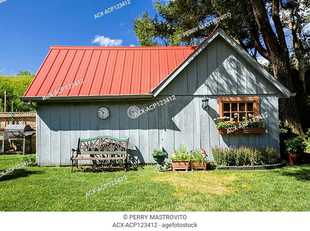 Old grey wood planked storage and garden shed with red standiing seam sheet metal roof in residential backyard in summer, Quebec, Canada