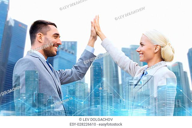 business, partnership, success, gesture and people concept - smiling businessman and businesswoman making high five over city and office buildings with charts...