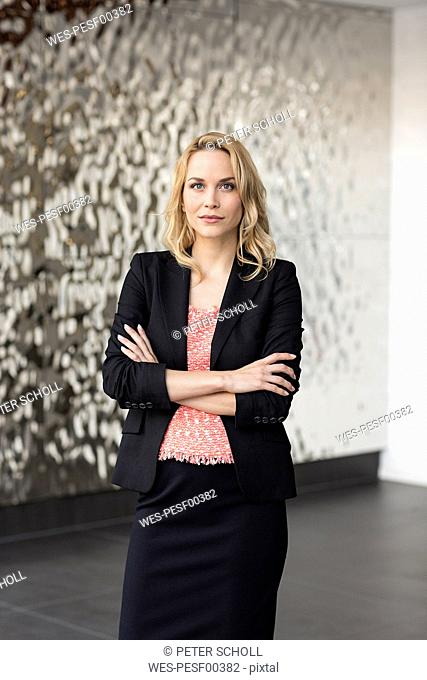 Portrait of confident businesswoman in front of rippled wall