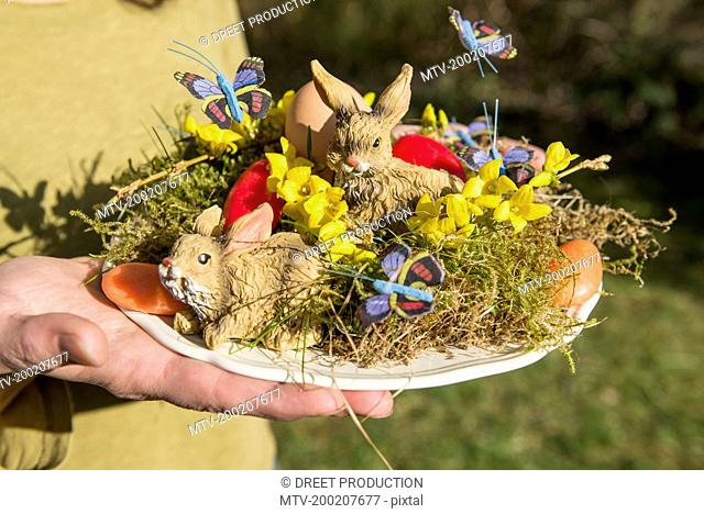 Close-up of a man holding Easter bunnies with Easter egg on nest