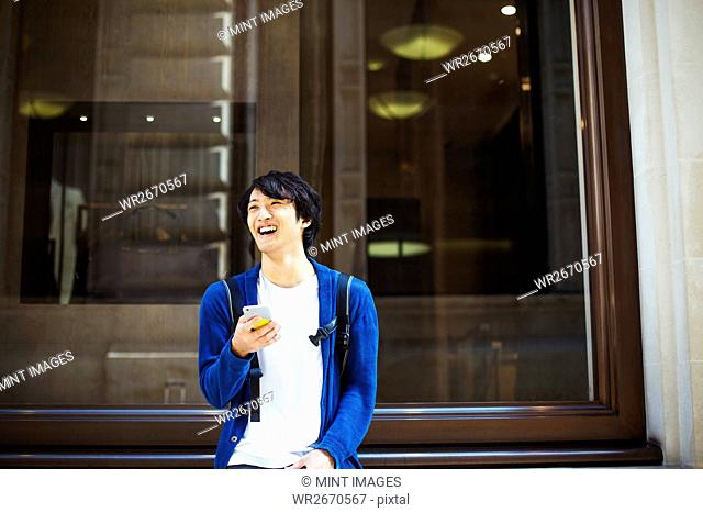 Young Japanese man enjoying a day out in London, using a smartphone