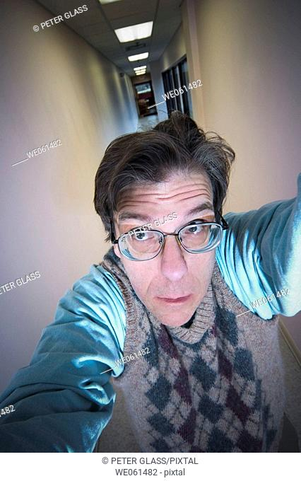Middle-age man, wearing glasses, posing in a long hallway