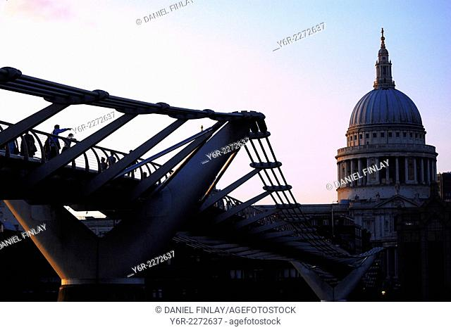 Visitors looking at St. Paul's Cathedral from the Millennium Bridge across the River Thames at dusk in the heart of London, England