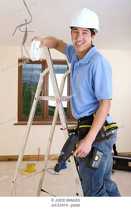 Electrician on ladder holding smoke detector and drill
