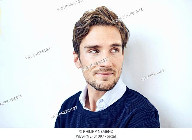 Portrait of smiling young man in front of white wall
