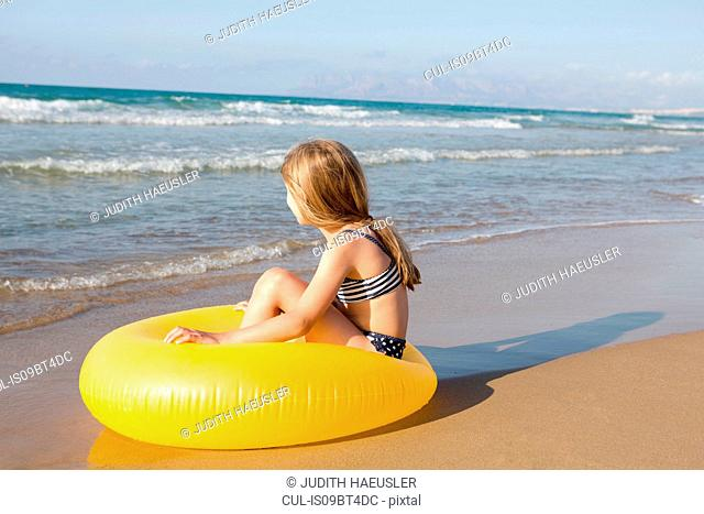 Girl sitting on yellow inflatable at beach, Castellammare del Golfo, Sicily, Italy