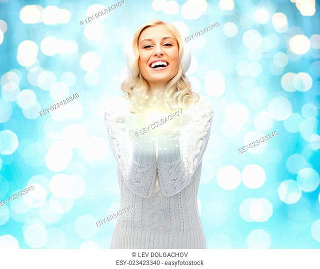 winter, magic, christmas and people concept - smiling young woman in earmuffs and sweater holding fairy dust on palms over blue holidays lights background