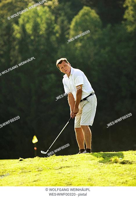 Austria, Male golfer swinging club on fairway