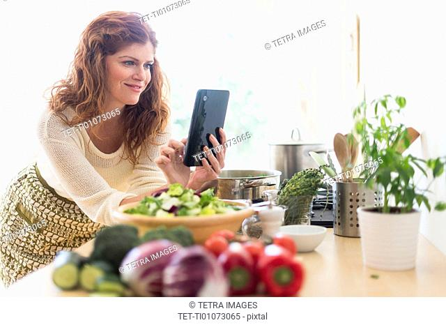 Woman cooking and using digital tablet in kitchen