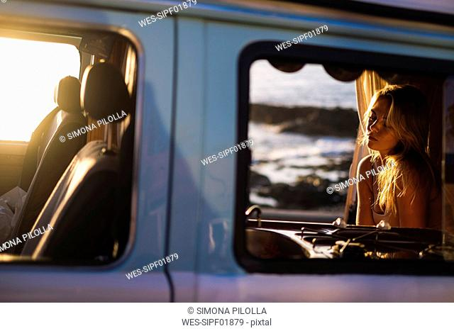 Spain, Tenerife, Blonde girl sitting in a van at sunset
