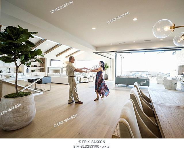 Older couple dancing in modern home