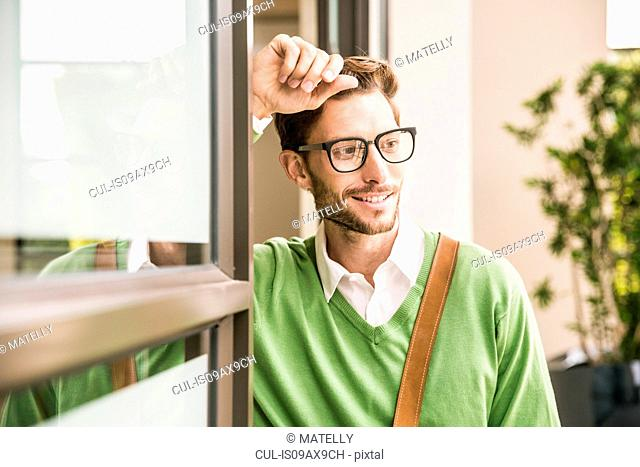 Cool businessman watching whilst leaning against office doorway