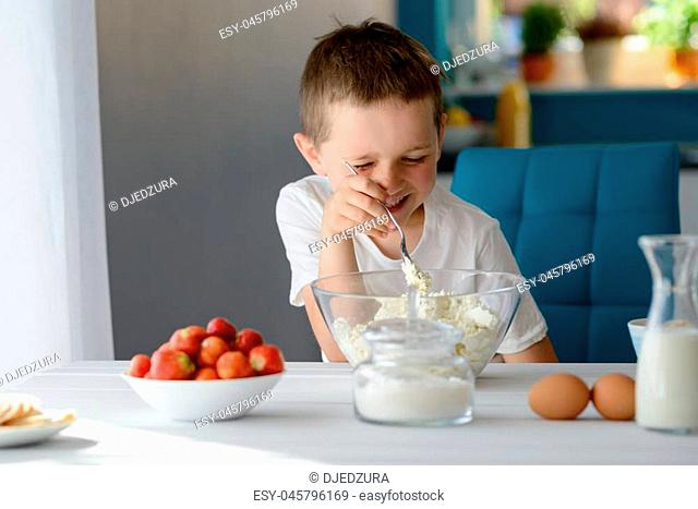 7 year old boy mixing white cottage cheese in a bowl. Prepares mini cheesecakes with strawberries