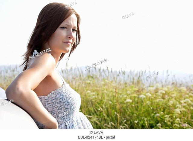 portrait of young woman in summer leaning against car