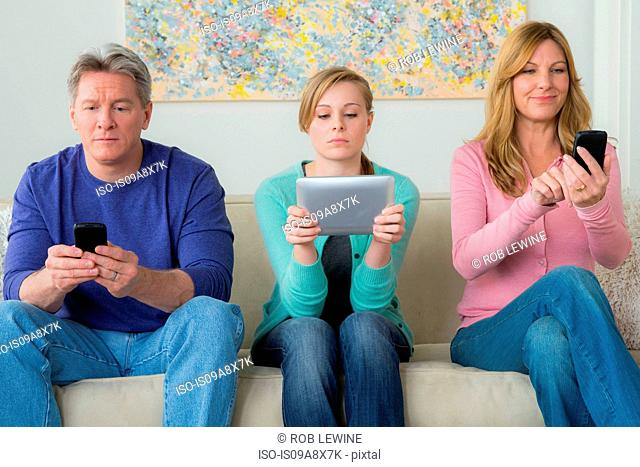 Family with teenage girl using communication devices