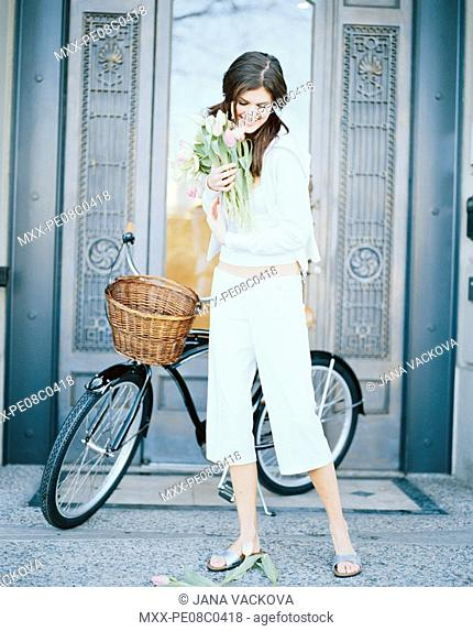 Woman standing beside bicycle with flowers in her hands