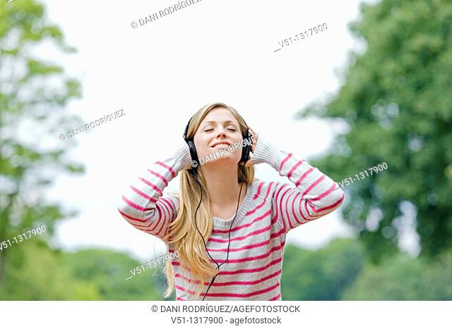 Portrait of a woman with closed eyes listening to music in the park